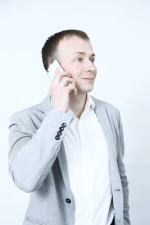 Smiling young man looking at his smart phone while text messaging on white background
