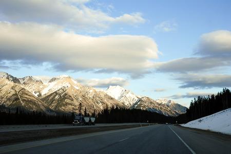 rockies: Road in the Evenin in Winter, Canadian Rockies, Alberta, Canada Stock Photo