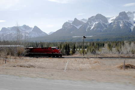 canmore: Freight Train Running along a Car, Canadian Rockies