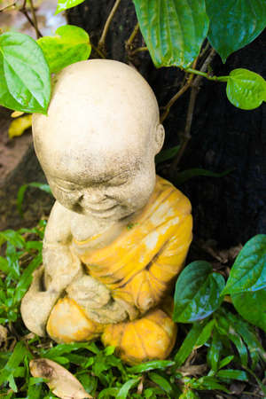Little monk sculpture under tree Stock Photo - 17038325