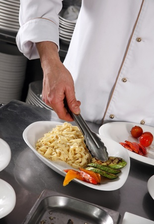 Chef preparing pasta on professional kitchen in restaurant