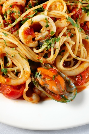 Pasta with tomato and seafood on white plate Stok Fotoğraf