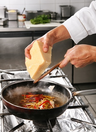grate: Chef grate cheese in pan on professional kitchen Stock Photo