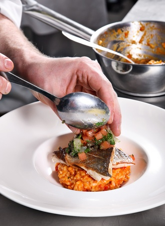 Chef decorate fish risotto on professional kitchen