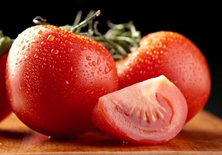 Tomate rojo con slice en detalle de la placa de madera Foto de archivo