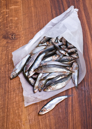 spat: Salted spat fish in paper smal bag on wood board Stock Photo