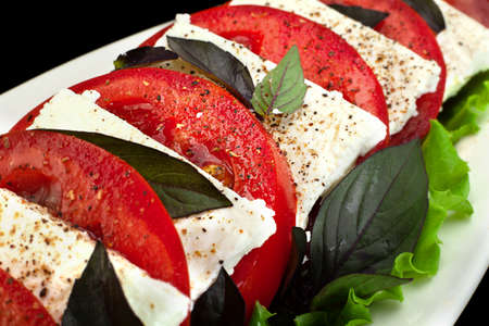 White Cheese appetizer with tomatoes slice and basil leaf