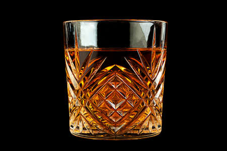 Wiskey beverage in glass isolated on black background