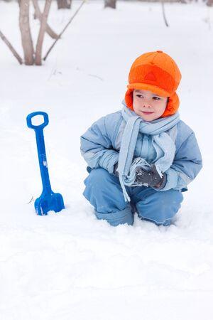 little boy playing snowballs, snowman sculpts, digs snow, photo