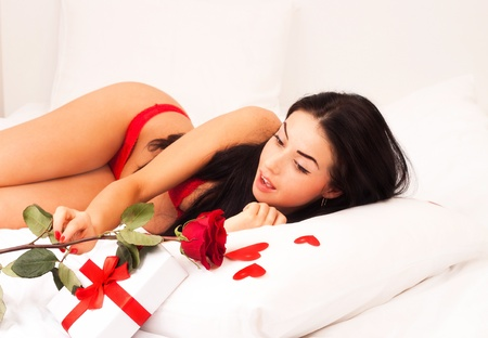 in love with a beautiful young girl lying in bed, strewn with hearts and roses. Feast day of St. Valentine  photo