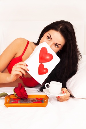 in love with a beautiful young girl lying in bed with gifts, cards, hearts, coffee, roses. Feast day of St. Valentine photo