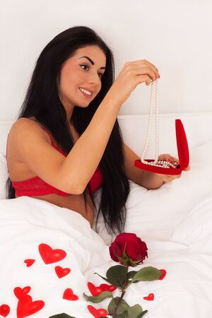 in love with a beautiful young girl lying in bed with gifts, cards, hearts, roses. Feast day of St. Valentine photo