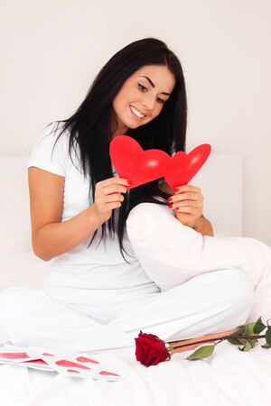 beautiful brunette woman at home was a gift from a loved one, postcard, heart. feast day of St. Valentine photo
