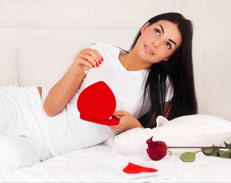 beautiful brunette woman at home was a gift from a loved one, jewelry, heart and roses. feast day of St. Valentine photo