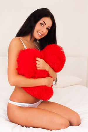 beautiful brunette woman at home hugging a big fluffy soft heart. feast day of St. Valentine photo