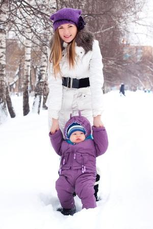 boule de neige: Girl, femme, mère, mère, amour, famille, voyage, vacances, blonde, un peu garçon, bébé, est assis dans la neige, boule de neige, baby boy, fils, Bonhomme de neige, neige, boules de neige, les flocons de neige, sculpter, creuser, un homme blanc, hiver, froid, parc, forêt, souriant, jouer, amusant, heureux, sun