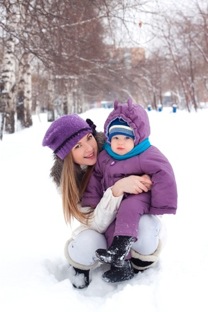 xmas baby: girl, woman, mother, mother, love, family, trip, vacation, blonde, a little boy, baby, sits in the snow, snowball, baby boy, son, snowman, snow, snowballs, snowflakes, sculpt, dig, a white man, winter, cold, park, forest, smiling, playing, fun, happy, sun