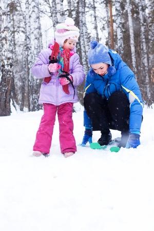 luge: Felice madre e figlia, la famiglia per una passeggiata in un parco di inverno, slittino, sci, pattinaggio, palle di neve