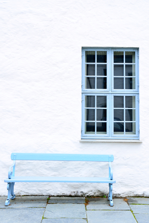 window bench: Light blue wooden bench and a window. White wall.