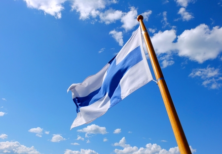 suomi: Flag of Finland on a wooden flagpole, blue sky.