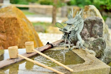 Japanese washbasin, tsukubai, with a dragon fountain and bamboo ladle.