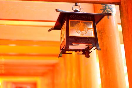 Lantern and red torii gates at Fushimi Inari, Kyoto, Japan.