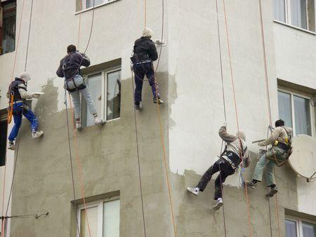 Pięciu pracowników budowlanych wiszące na linie z wysokiego budynku