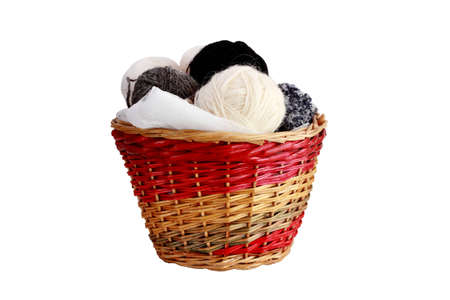 basket embroidery: The basket is filled with yarn hanks for knitting  Natural wool is prepared for needlework  It is isolated on a white background  Stock Photo