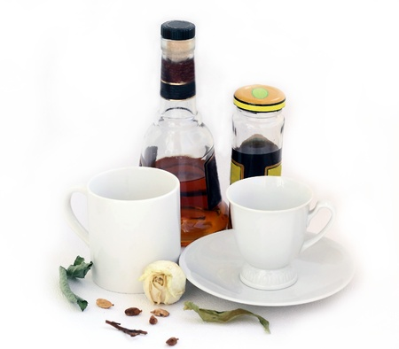 chicory coffee: White mug for tea and a white cup for coffee on a saucer  The started cognac and chicory,   faded rose and some grains of cardamom  Stock Photo