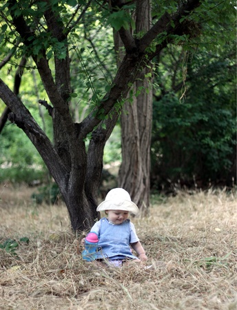 under a tree: The little girl sits in a grass under a tree and smiles  Vertical photo