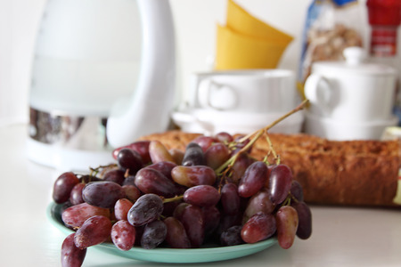 electric kettle:  Grapes on a white background utensils, electric kettle and a baguette. Stock Photo