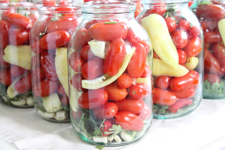 Tomatoes, greens, pepper sweet in glass jars. Preparation for preservation.