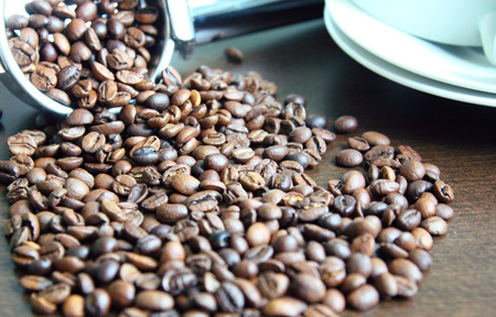 coffee spill: Coffee beans spill out of the dimensional, metal spoons and lie loose on the table.