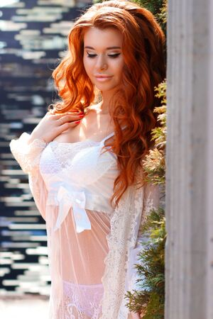 peignoir: young beautiful redhead girl in a peignoir in the room