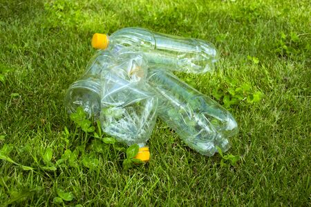 Plastic bottles lie on the green grass. Pollution of nature. Rubbish on the lawn.