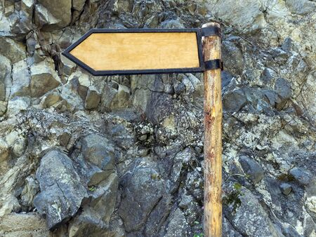 A wooden signpost shows the direction of the path in the mountains. Campaign