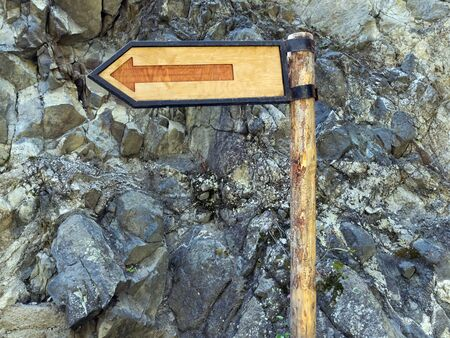 A wooden signpost shows the direction of the path in the mountains. Campaign Orienteering. Archivio Fotografico - 132122298