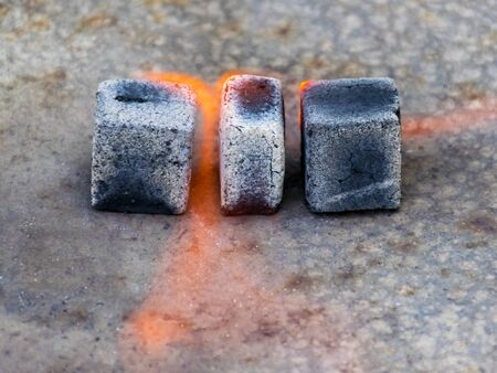 Coals for a hookah in fire and smoke. Black coals burn beautifully. Ignition of coal. Rest and relaxation.