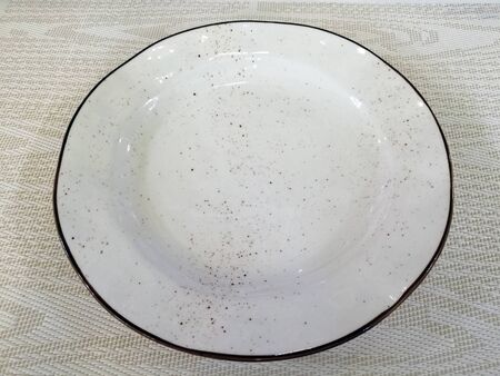 A white ceramic dish with a brown rim and brown spray. Beautiful tableware. Kitchen utensils. Banco de Imagens - 132124383