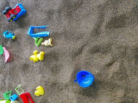 Multi-colored plastic toys in the sand. Childrens toys for games in the sand and on the beach. Bucket, spade and rake. Children playground.