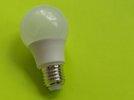 Energy saving lamp on a green background. Electric bright bulb. Devices for lighting. Electricity. Фото со стока