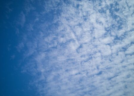 Beautiful white cirrus clouds on a blue sky. Autumn sky and good weather. Background. Фото со стока