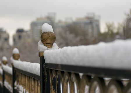 The first snow lies on the railing of metal near the river in the city. Frozen railing. Cold winter 写真素材