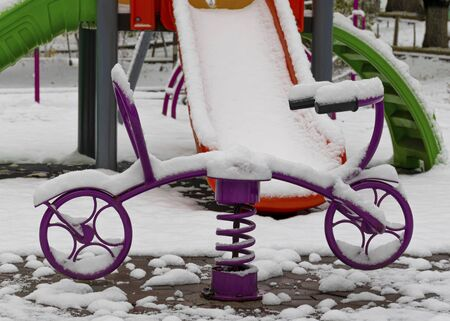 The playground is covered in snow. Childrens slide and stairs. Happy childhood. Winter and snowfall. 写真素材