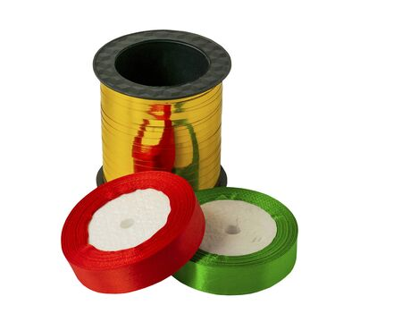 Roll of satin ribbon for decorating gifts on a white background. Silk and satin ribbon of gold, red and green.