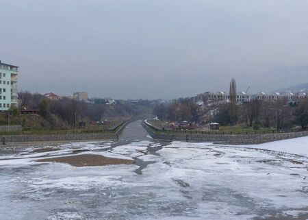 Frozen river in the city in cloudy weather. Winter has come. City landscape in the cold winter. Фото со стока