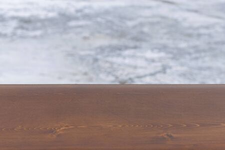 Brown wooden board with blurry winter background of a frozen river. Cold weather. Wood surface for design.  写真素材
