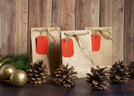 Vintage handmade gift boxes made of kraft paper on a wooden background in the Christmas style, decorated with golden Christmas balls, cones, fir branch. Christmas, New Year, winter holiday. Kraft package, holiday concept, top view, flat lay. Mocap. Stock Photo