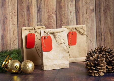 Vintage handgemachte Geschenkboxen aus Kraftpapier auf Holzuntergrund im Weihnachtsstil, verziert mit goldenen Weihnachtskugeln, Zapfen, Tannenzweig. Weihnachten, Neujahr, Winterurlaub. Kraftpaket, Urlaubskonzept, Draufsicht, flache Lage. Mocap.