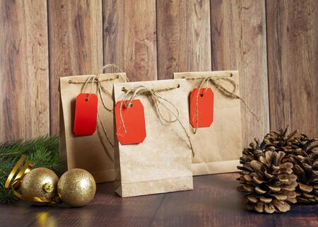 Vintage handmade gift boxes made of kraft paper on a wooden background in the Christmas style, decorated with golden Christmas balls, cones, fir branch. Christmas, New Year, winter holiday. Kraft package, holiday concept, top view, flat lay. Mocap.